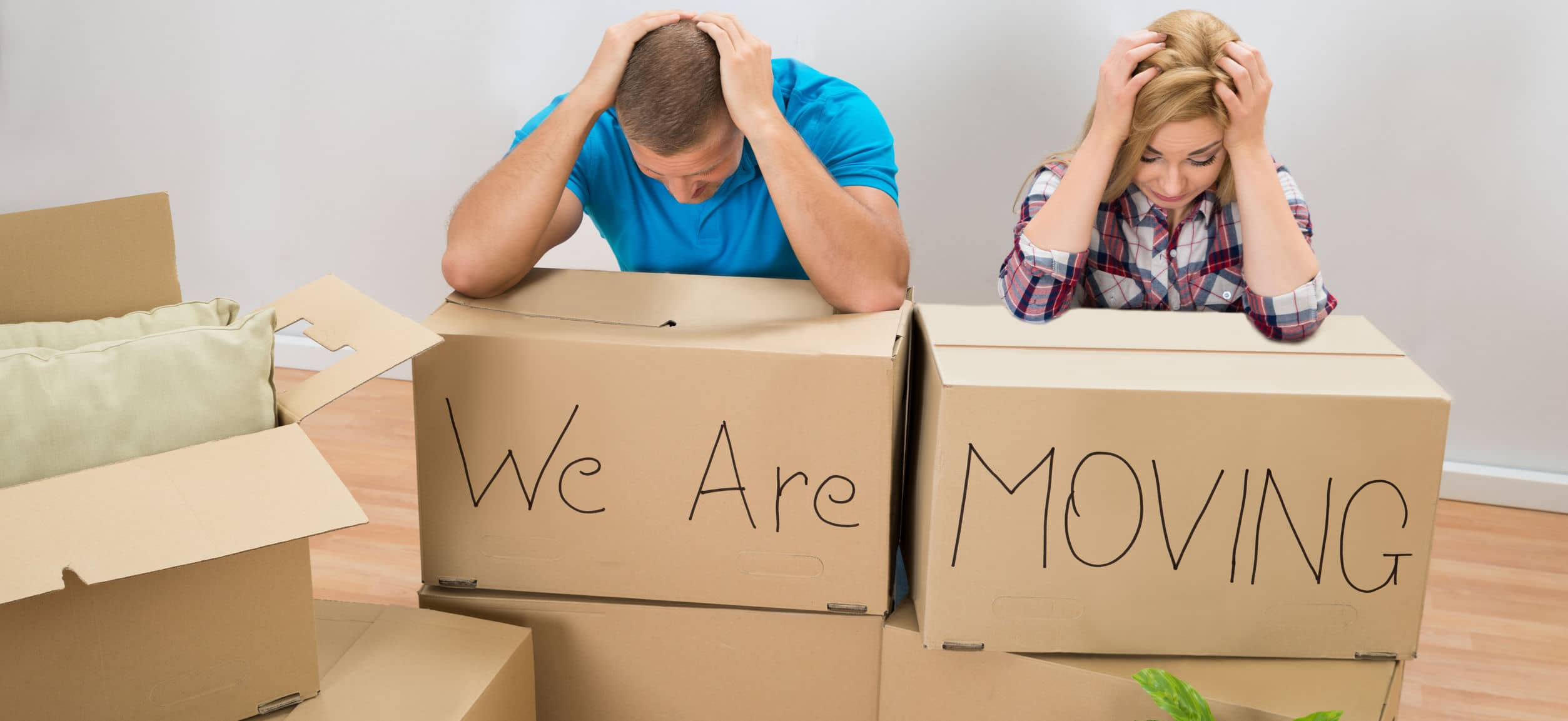 Couple holding their heads out of stress behind moving boxes