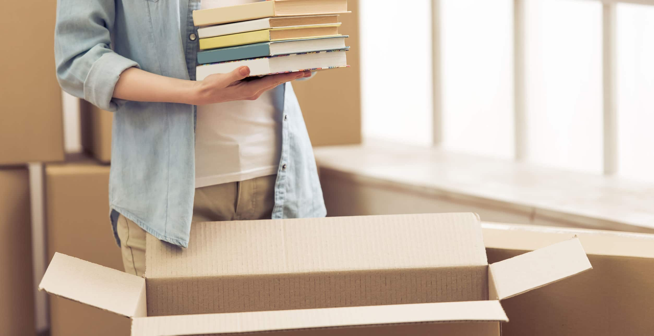 Woman in a house unpacking books