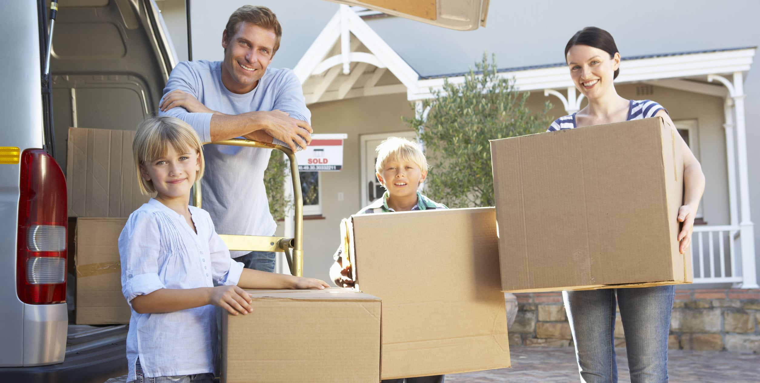 Family standing in front of house with moving boxes