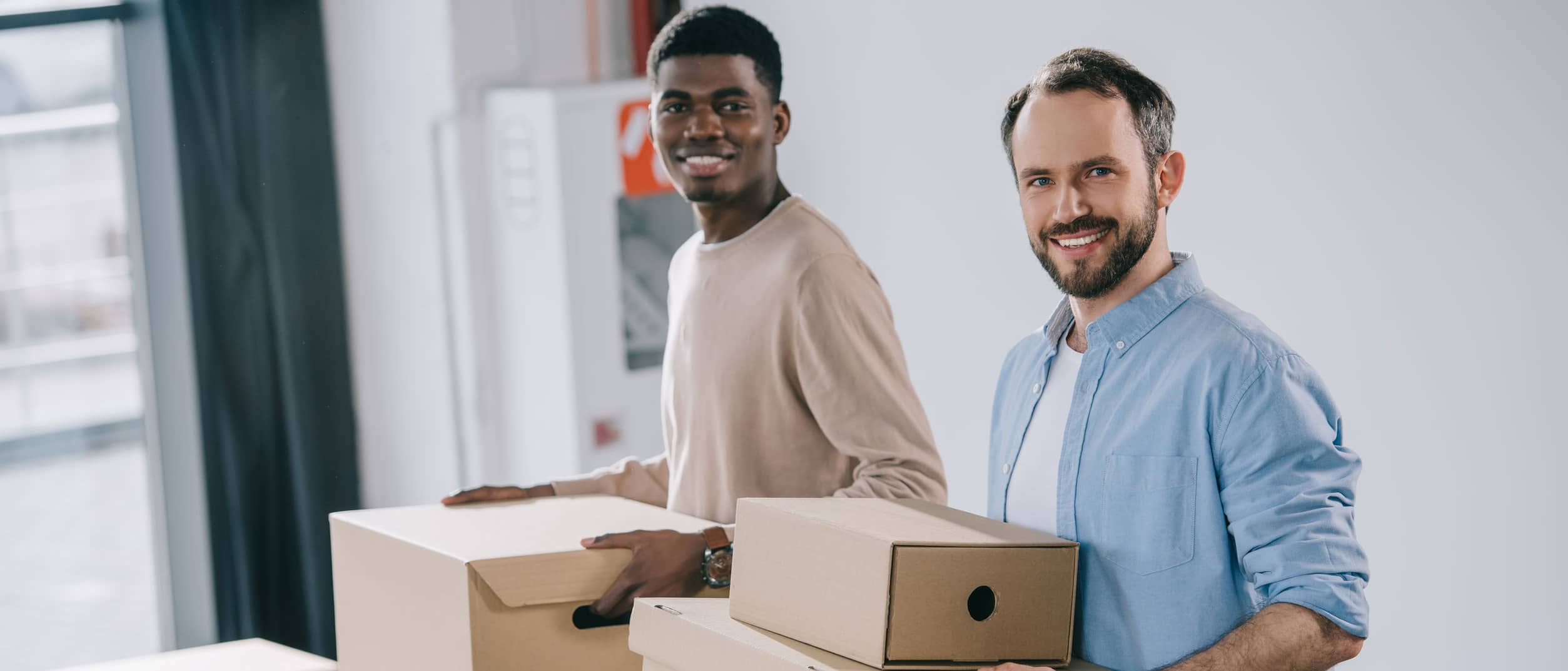 Two men moving boxes out of an office