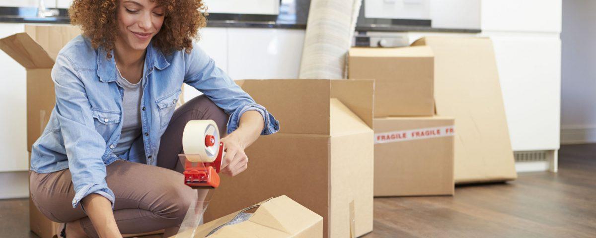 Woman taping a moving box shut
