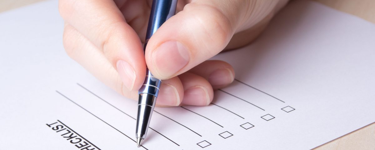 Closeup of hand filling out a checklist