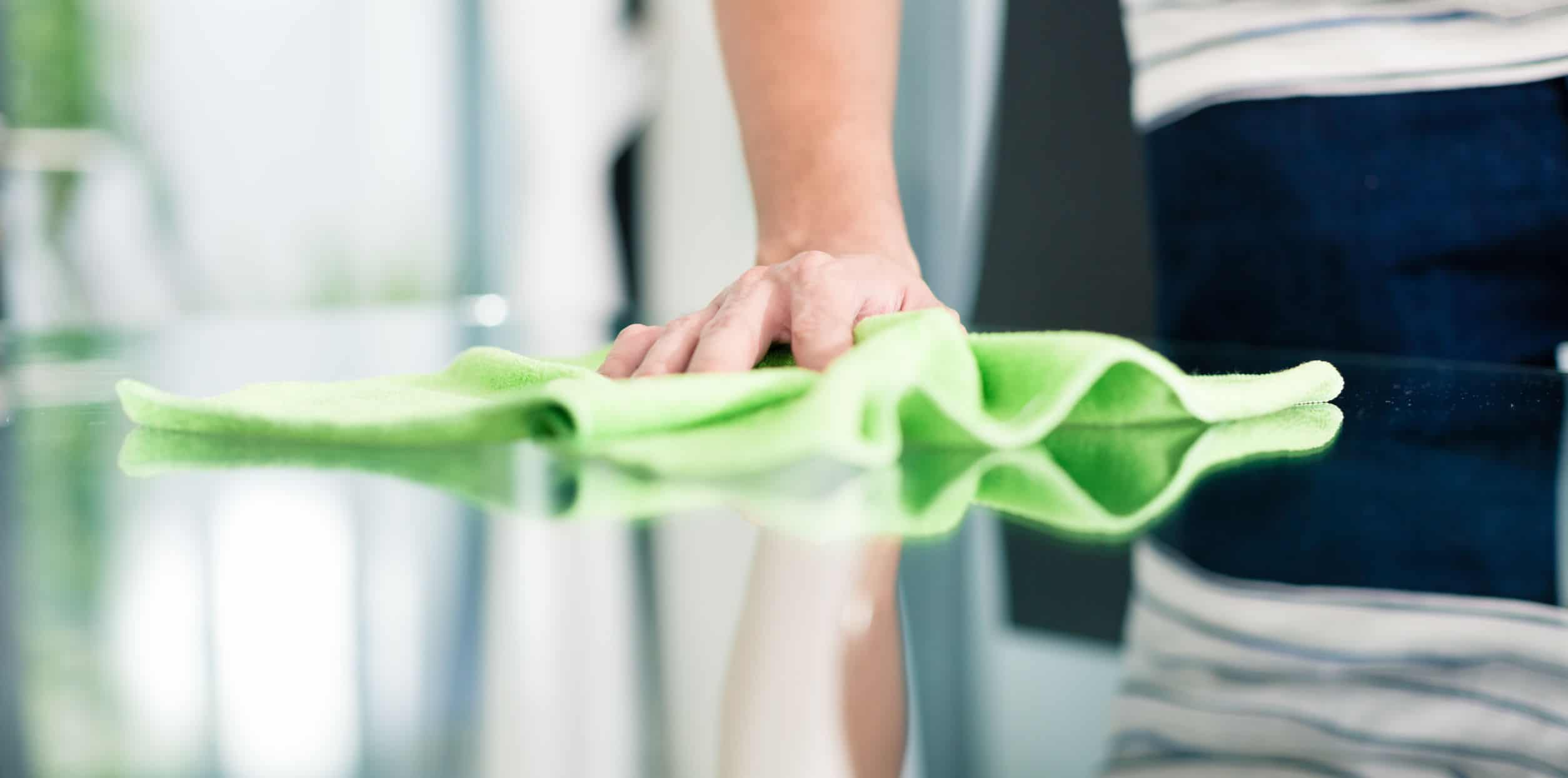 Man cleaning table in home with cloth
