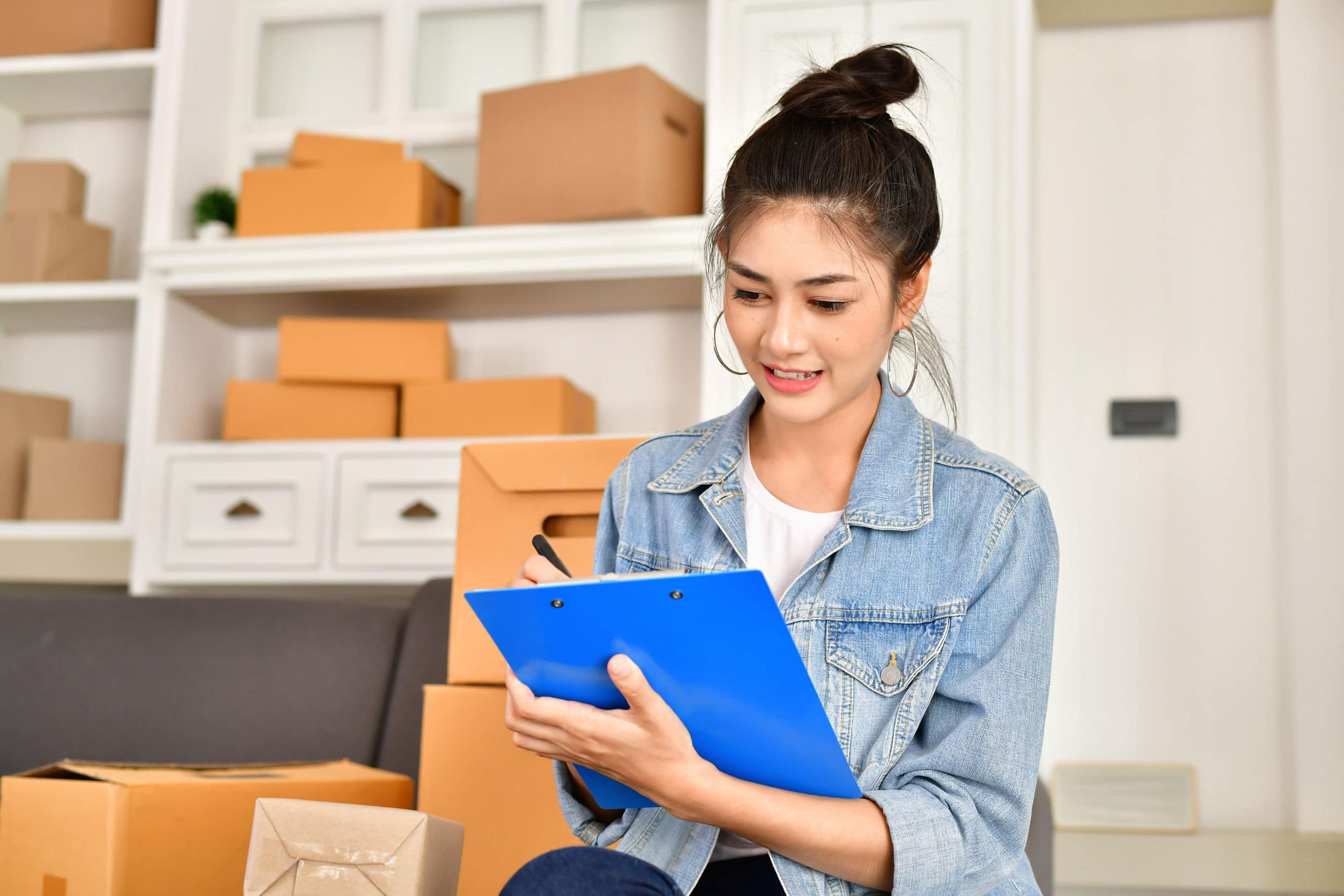 Woman with moving boxes writing a checklist