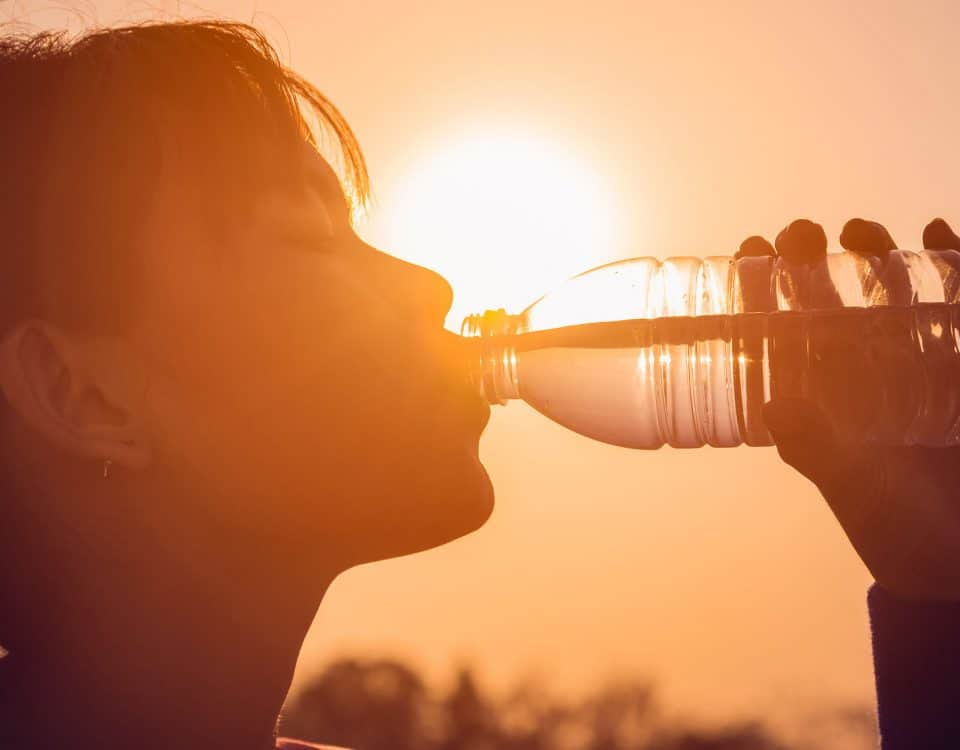 Woman out in the sun drinking a bottle of water