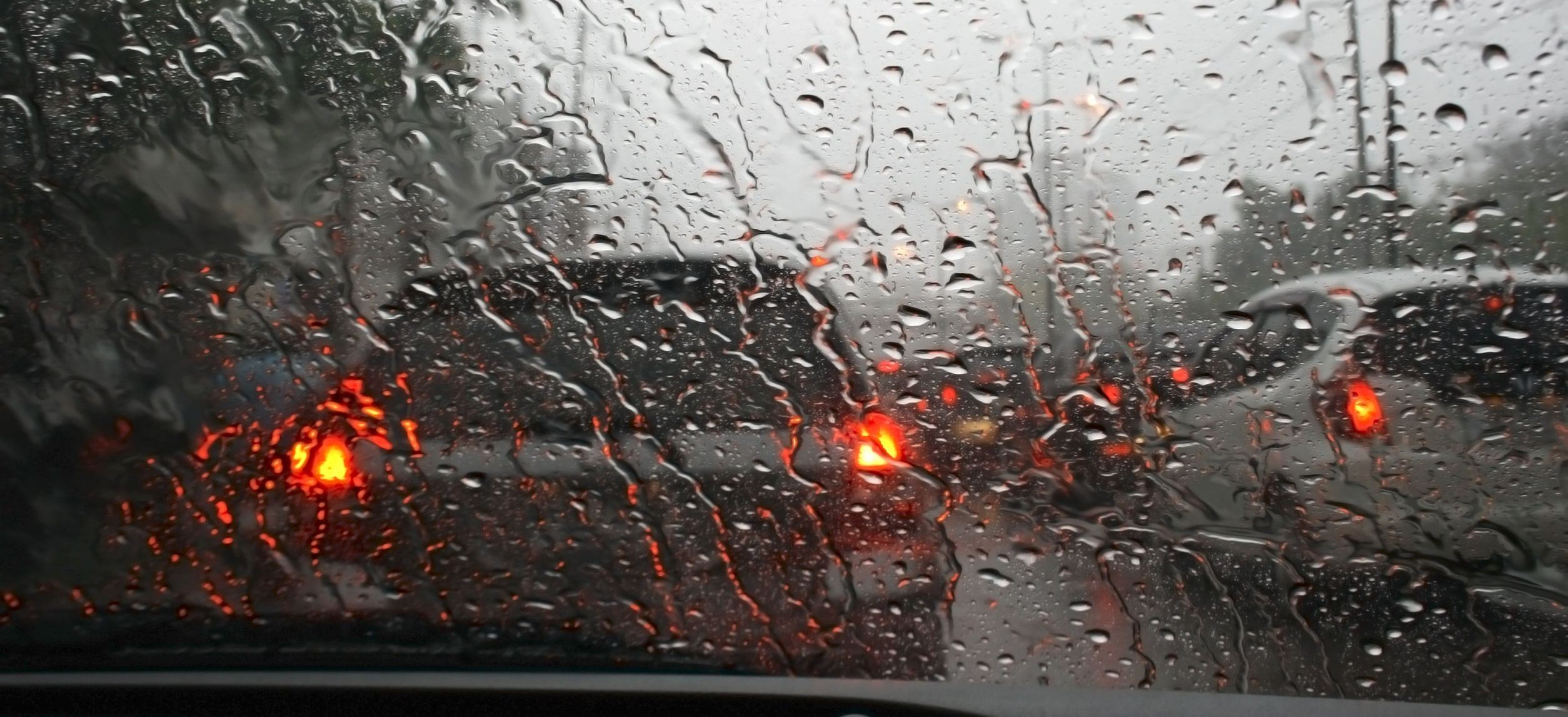 Road view through car window with rain drops