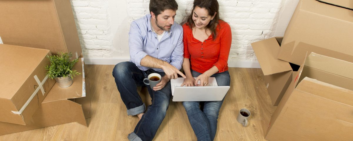 Couple on a laptop sitting by moving boxes