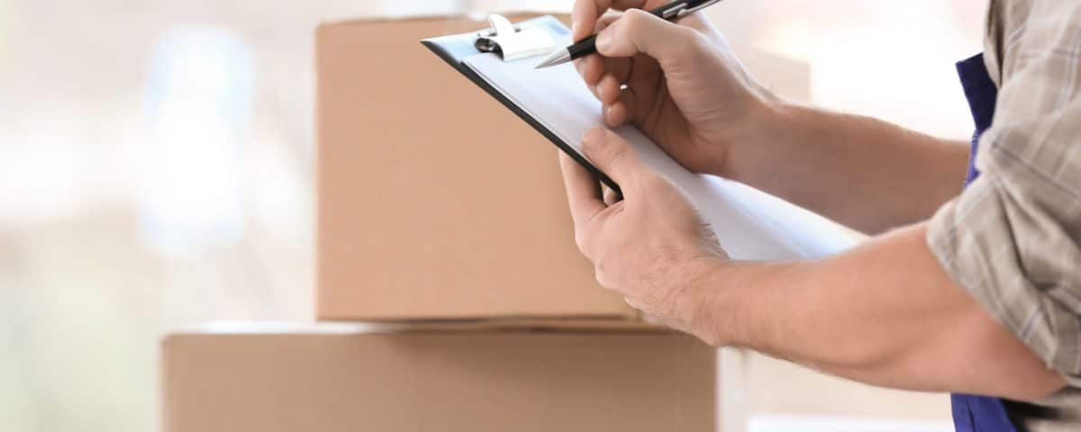 Man holding clipboard on boxes background