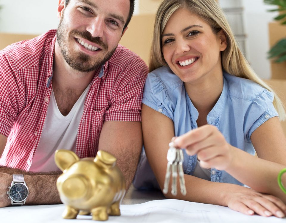 Couple holding keys to new house in front of piggy bank